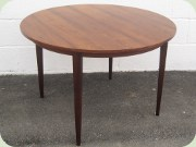 Round dining table with extension leaves, rosewood imitating laminate.