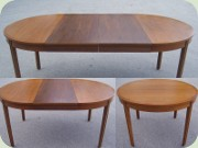Round walnut veneered dining table with extension leaves